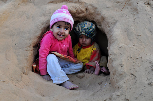 Children enjoying in sand cave
